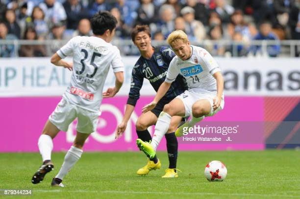 Akito Fukumori of Consadole Sapporo and Shun Nagasawa of Gamba Osaka compete for the ball during the JLeague J1 match between Gamba Osaka and...