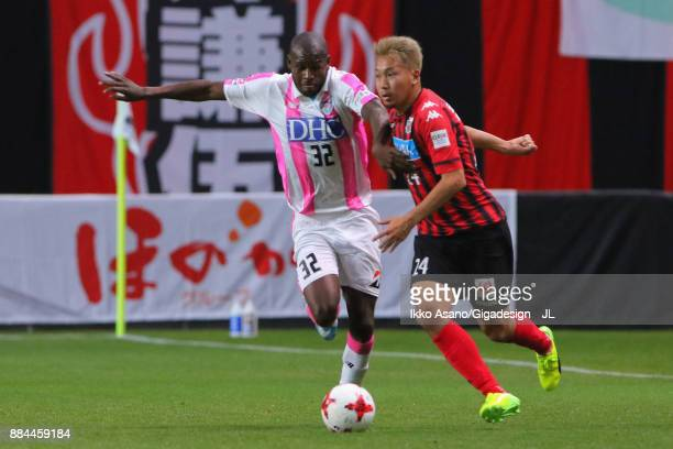 Akito Fukumori of Consadole Sapporo and Victor Ibarbo of Sagan Tosu compete for the ball during the JLeague J1 match between Consadole Sapporo and...