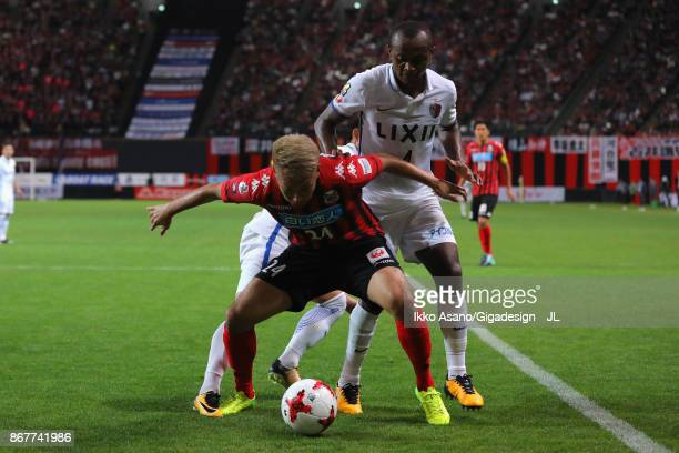 Akito Fukumori of Consadole Sapporo controls the ball under pressure of Leo Silva of Kashima Antlers during the JLeague J1 match between Consadole...