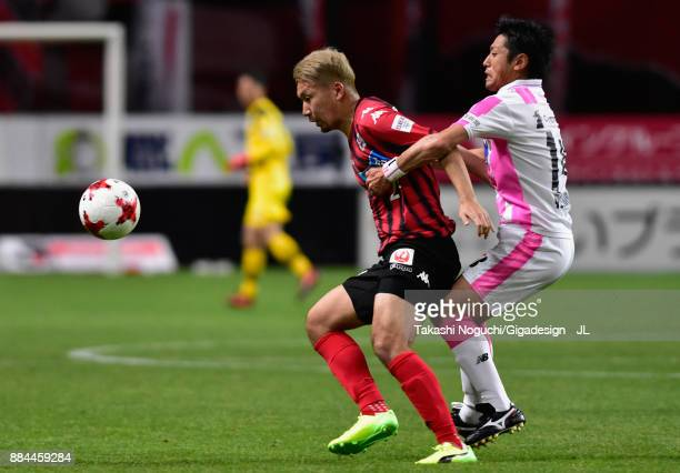 Akito Fukumori of Consadole Sapporo controls the ball under pressure of Yoshiki Takahashi of Sagan Tosu during the JLeague J1 match between Consadole...