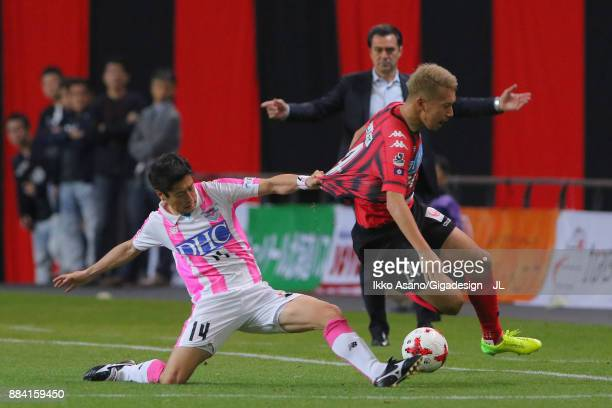 Akito Fukumori of Consadole Sapporo is challenged by Yoshiki Takahashi of Sagan Tosu during the JLeague J1 match between Consadole Sapporo and Sagan...