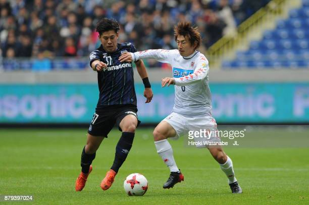 Akito Takagi of Gamba Osaka and Shingo Hyodo of Consadole Sapporo compete for the ball during the JLeague J1 match between Gamba Osaka and Consadole...