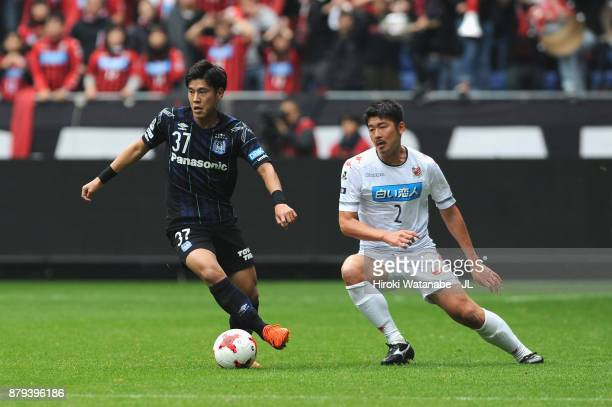 Akito Takagi of Gamba Osaka controls the ball under pressure of Tomonobu Yokoyama of Consadole Sapporo during the JLeague J1 match between Gamba...