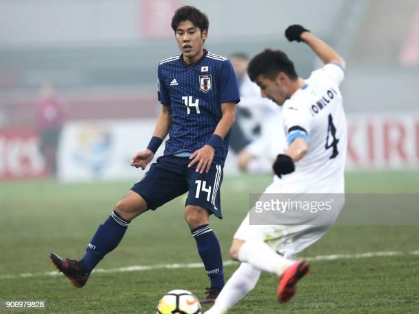 Akito Takagi of Japan challenges Akramjon Komilov of Uzbekistan during their AFC Under23 Championship football match at Nanjing in China's Jiangsu...