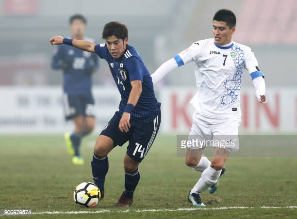 Akito Takagi of Japan fights for the ball with Odiljon Xamrobekov of Uzbekistan during their AFC Under23 Championship football match at Nanjing in...