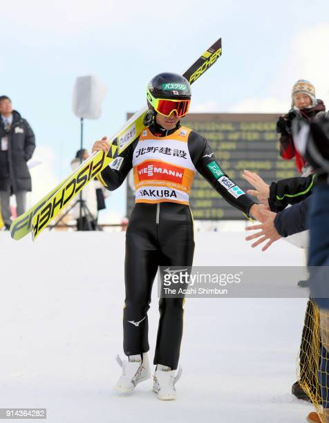 Akito Watabe of Japan high fives with supporters after competing in the jump of the Individual Gundersen LH134/10km during day two of the FIS Nordic...