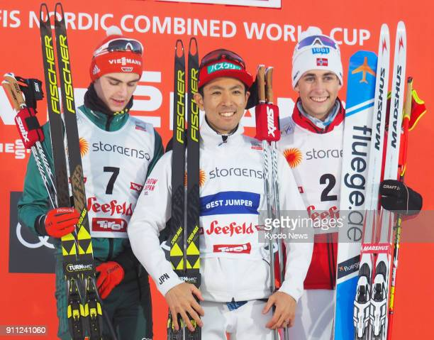 Akito Watabe of Japan poses on the podium after winning a Nordic combined skiing World Cup event in Seefeld Austria on Jan 27 alongside runnerup...
