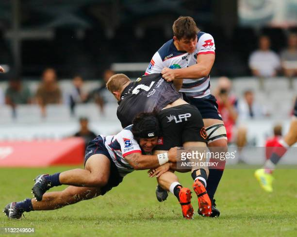 Akker van der Merwe of the Cell C Sharks is tackled by Richard Hardwick and Anaru Rangi of the Melbourne Rebels during the Super Rugby match...