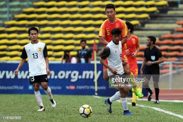 Akkhom Thoranin of Laos shields the ball from Li Yang of China during the AFC U23 Championship qualifier between China and Laos at Shah Alam Stadium...