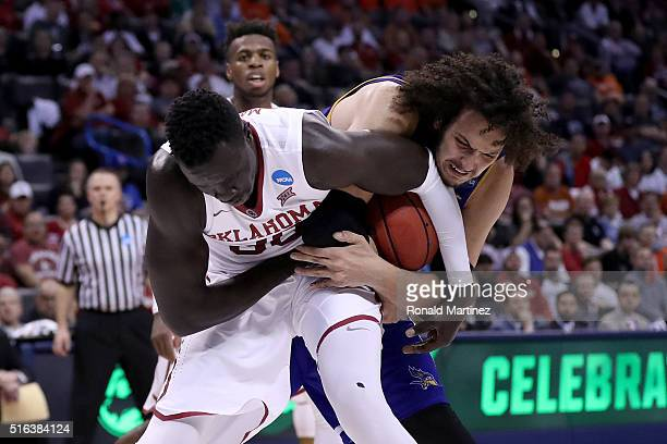 Akolda Manyang of the Oklahoma Sooners and Aly Ahmed of the Cal State Bakersfield Roadrunners battle for the ball in the second half in the first...