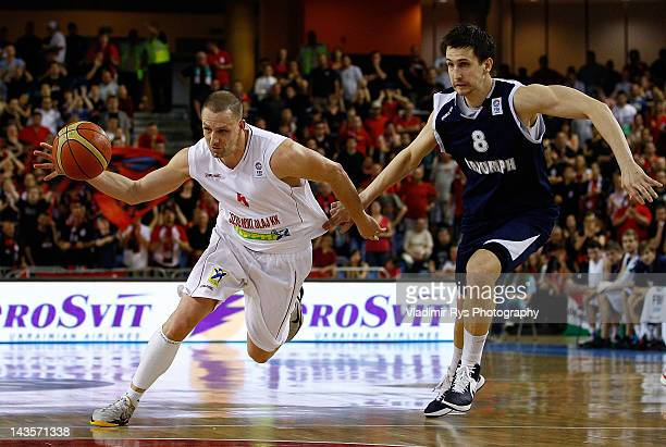 Akos Horvath of Szolnoki attacks as Artem Kuzyakin of Triumph defends during the FIBA Europe EuroChallenge Final Four third place game between...