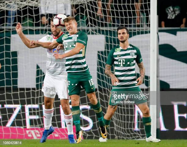 Akos Kinyik of DVSC battles for the ball in the air with David Siger of Ferencvarosi TC in front of Davide Lanzafame of Ferencvarosi TC during the...