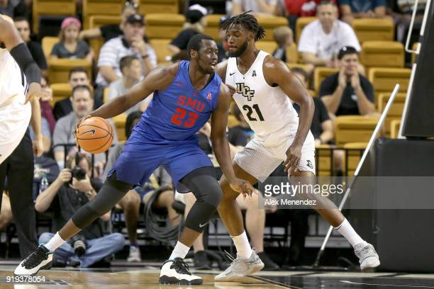 Akoy Agau of the Southern Methodist Mustangs dribbles in front of Chad Brown of the UCF Knights during a NCAA basketball game at the CFE Arena on...