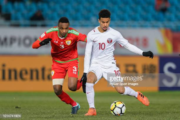 Akram Afif of Qatar runs with the ball being defended by Majid Al Saadi of Oman during the AFC U23 Championship China 2018 Group A match between Oman...