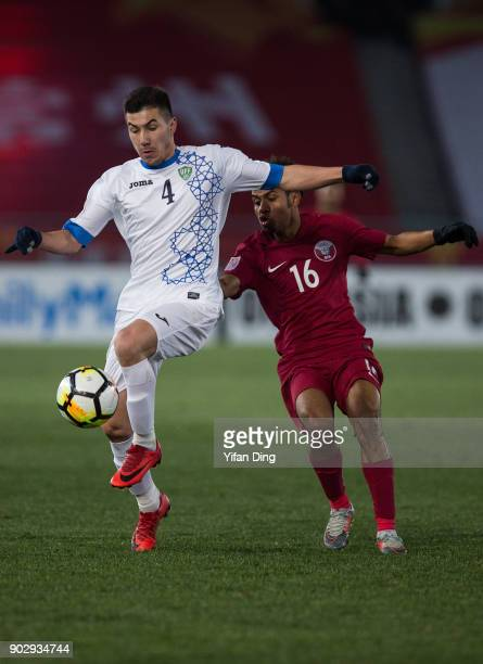 Akramjon Komilov of Uzbekistan and Hisham Ali of Qatar in action during the AFC U23 Championship Group A match between Qatar and Uzbekistan at...