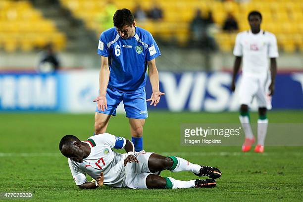 Akramjon Komilov of Uzbekistan appeals to Roger Gomis of Senegal after going down injured during the FIFA U20 World Cup New Zealand 2015 quarterfinal...