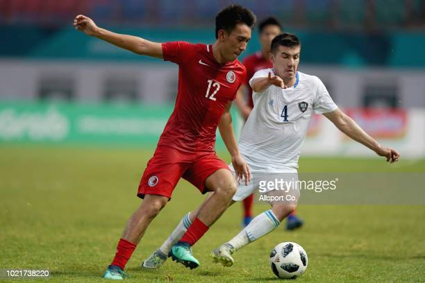 Akramjon Komilov of Uzbekistan holds off Wu Chun Ming of Hong Kong China during the Men's football competition of the last 16 elimination match...