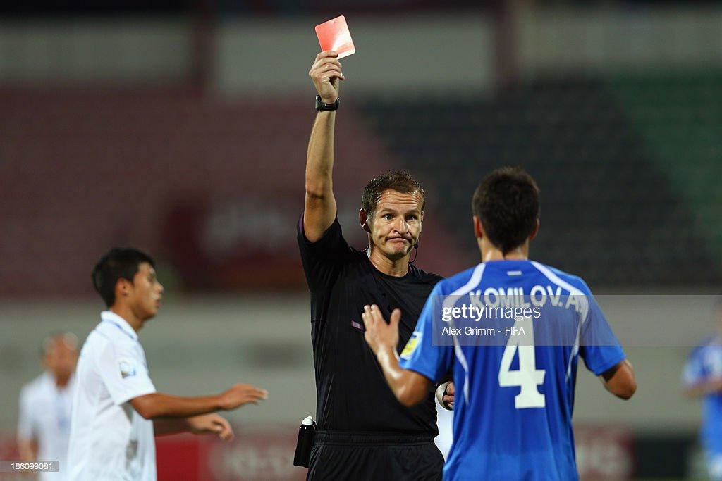Akramjon Komilov of Uzbekistan is sent off by referee Pavel Kralovec during the FIFA U-17 World Cup UAE 2013 Round of 16 match between Honduras and Uzbekistan at Sharjah Stadium on October 28, 2013 in Sharjah, United Arab Emirates.