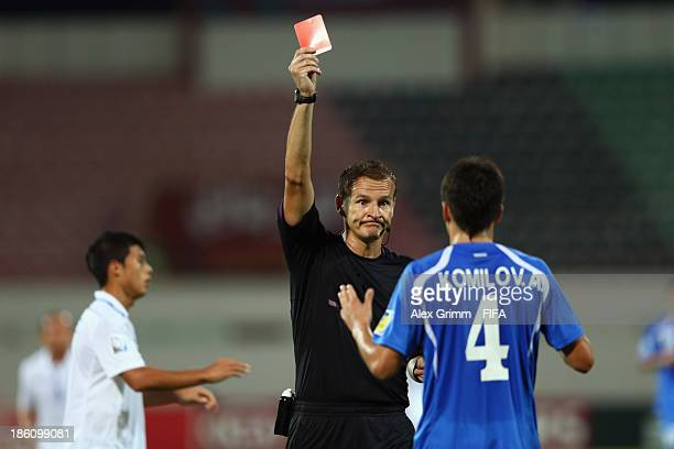 Akramjon Komilov of Uzbekistan is sent off by referee Pavel Kralovec during the FIFA U17 World Cup UAE 2013 Round of 16 match between Honduras and...