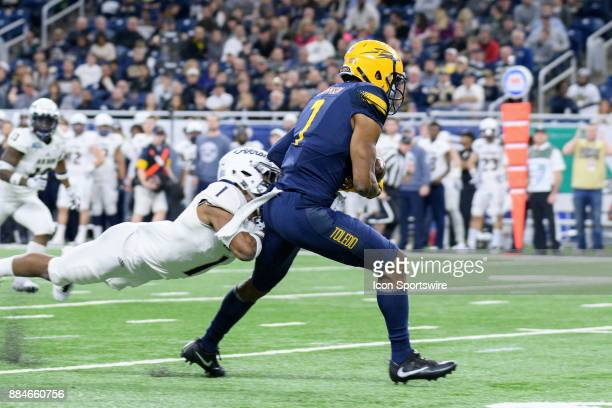 Akron Zips CB Alvin Davis attempts to tackle Toledo Rockets WR Jon'Vea Johnson in the MAC Championship game between Akron Zips and Toledo Rockets on...