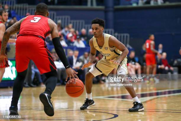 Akron Zips guard Loren Cristian Jackson defends Ball State Cardinals guard Josh Thompson during the second half of the men's college basketball game...