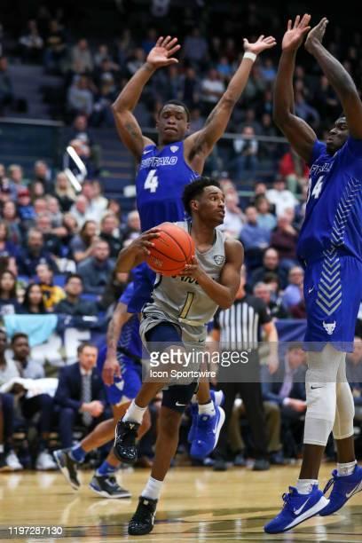 Akron Zips guard Loren Cristian Jackson looks to pass as Buffalo Bulls guard Davonta Jordan and Buffalo Bulls forward Josh Mballa defend during the...