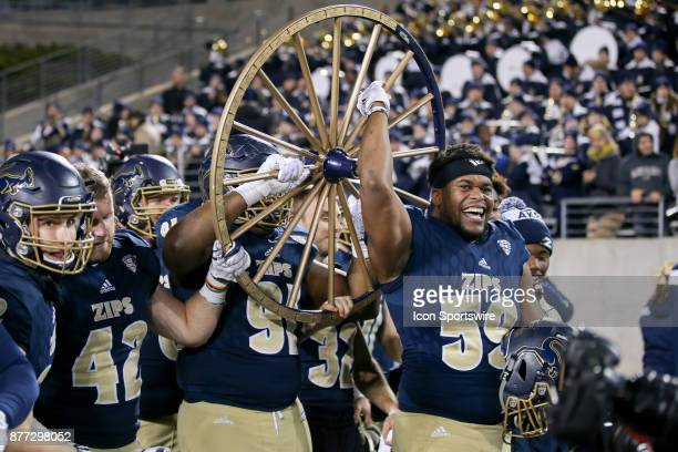 Akron Zips linebacker Andrew Hauser Akron Zips defensive lineman Ibrahima Camara and Akron Zips offensive lineman Trevor Brown hoist the Wagon Wheel...