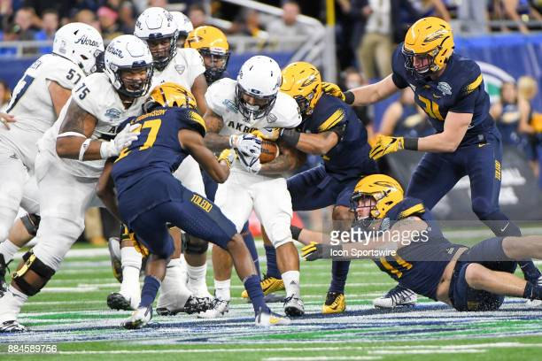 Akron Zips quarterback Kato Nelson is swarmed by the Toledo Rockets defense during the Akron Zips versus Toledo Rockets MAC Championship Game on...