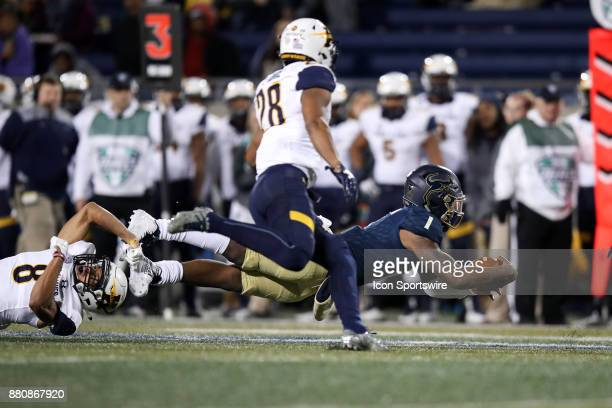 Akron Zips quarterback Kato Nelson lunges for a first down as he is tackled by Kent State Golden Flashes defensive back Elvis Hines during the first...