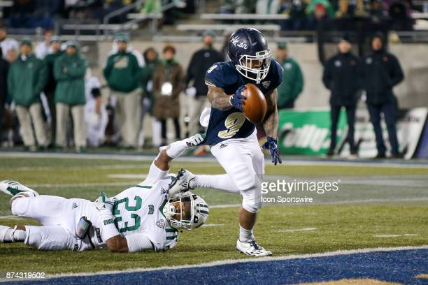 Akron Zips running back Manny Morgan eludes the tackle attempt of Ohio Bobcats safety Kylan Nelson to score a touchdown during the fourth quarter of...