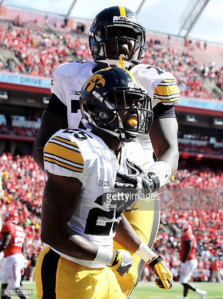 Akrum Wadley of the Iowa Hawkeyes is congratulated by teammate James Daniels after Wadley scored the game winning touchdown against the Rutgers...