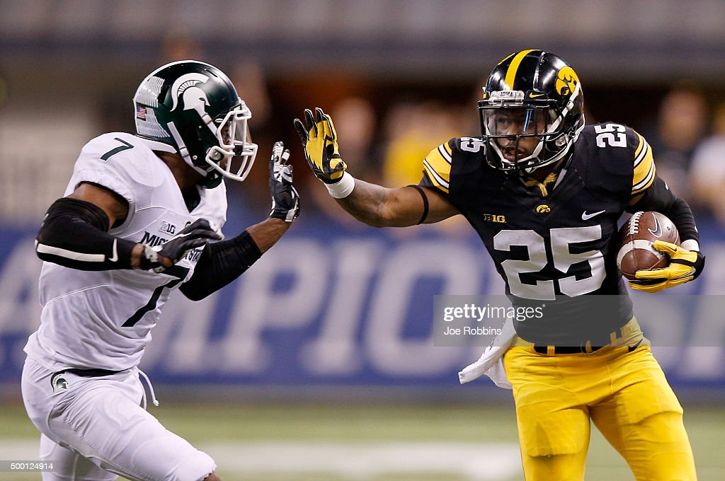 Akrum Wedley #25 of the Iowa Hawkeyes attempts to fend off Demetrious Cox #7 of the Michigan State Spartans in the Big Ten Championship at Lucas Oil Stadium on December 5, 2015 in Indianapolis, Indiana.
