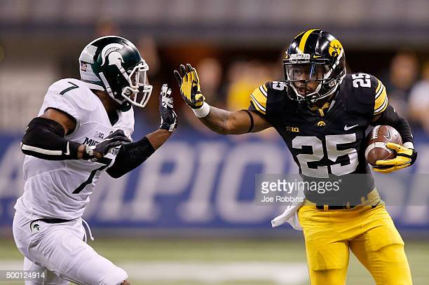 Akrum Wedley of the Iowa Hawkeyes attempts to fend off Demetrious Cox of the Michigan State Spartans in the Big Ten Championship at Lucas Oil Stadium...