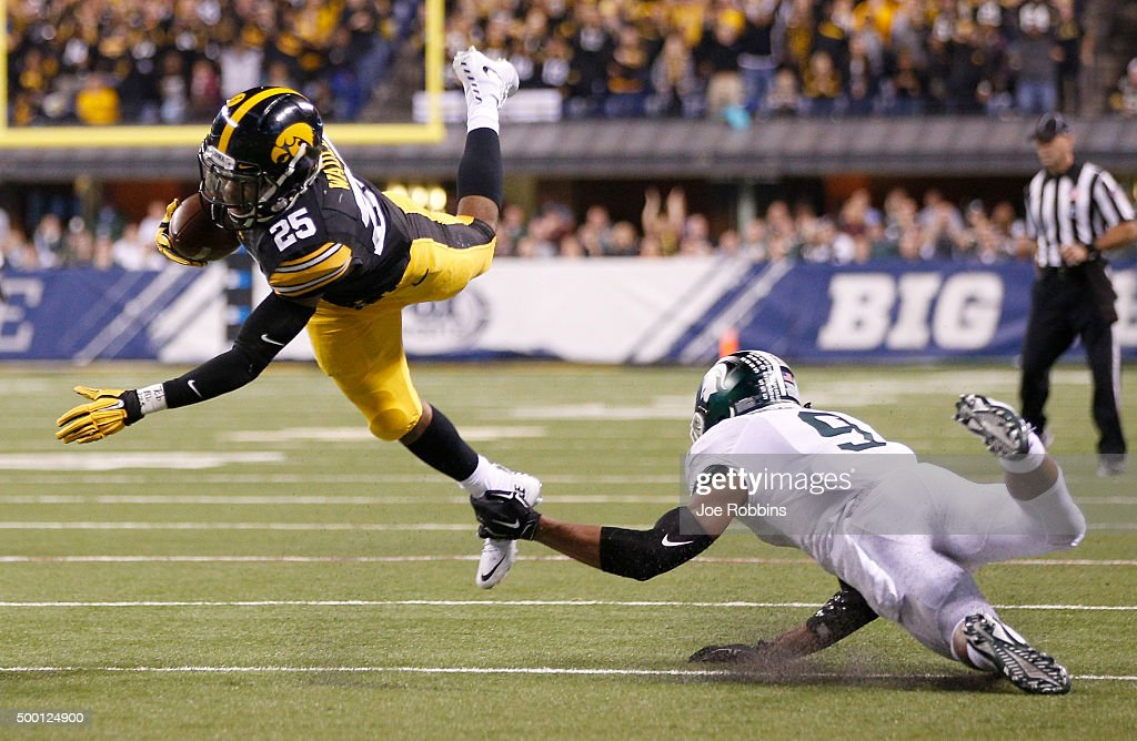 Akrum Wedley #25 of the Iowa Hawkeyes leaps to avoid a tackle attempt by Montae Nicholson #9 of the Michigan State Spartans in the Big Ten Championship at Lucas Oil Stadium on December 5, 2015 in Indianapolis, Indiana.