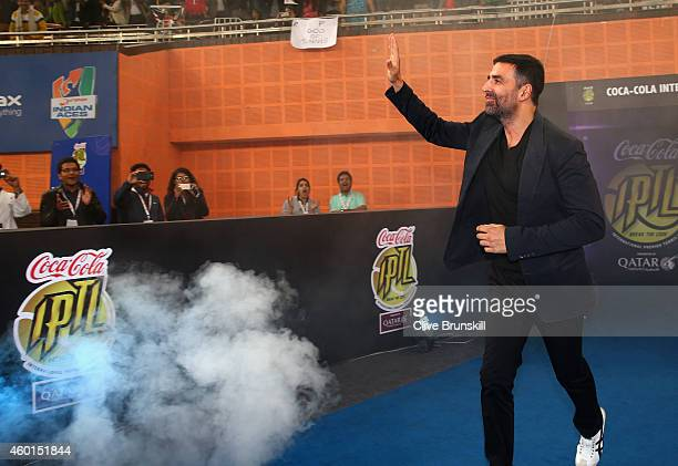 Akshay Kumar walks on court to play tennis with Roger Federer of the Indian Aces during the CocaCola International Premier Tennis League third leg at...