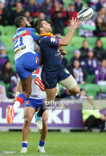Akuila Uate of the Knights and Maurice Blair of the Storm contest for the ball during the round 14 NRL match between the Melbourne Storm and the...
