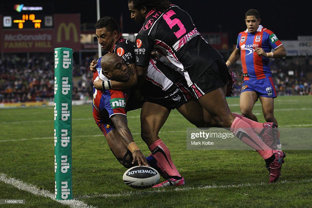 Akuila Uate of the Knights is tackled by Benji Marshall and Lote Tuqiri of the Tigers as he scores a try during the round 16 NRL match between the Newcastle Knights and the Wests Tigers at Hunter Stadium on June 25, 2012 in Newcastle, Australia.