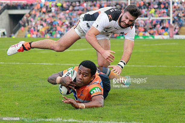 Akuila Uate of the Knights scores a try in front of James Tedesco of the Tigers during the round 13 NRL match between the Newcastle Knights and the...