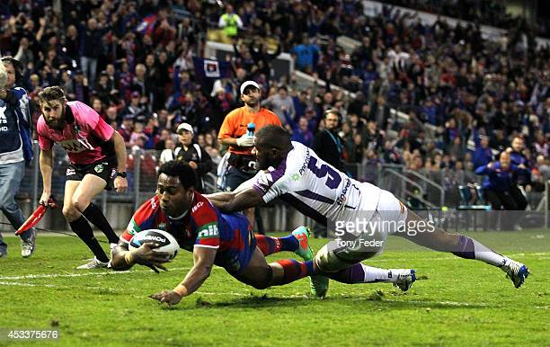 Akuila Uate of the Knights scores a try with seconds to go during the round 22 NRL match between the Newcastle Knights and the Melbourne Storm at...
