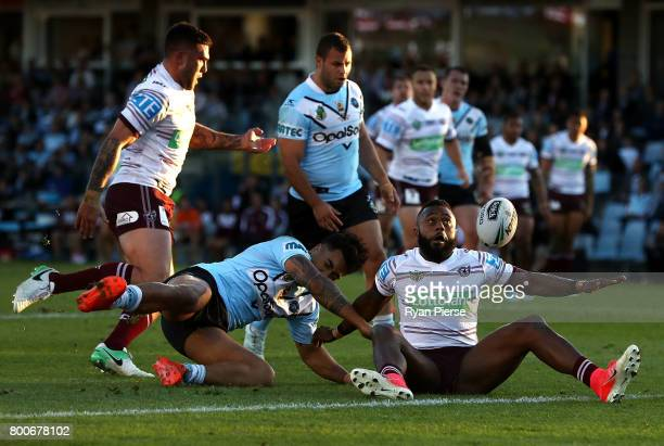 Akuila Uate of the Sea Eagles is tackled by Sosaia Feki of the Sharks during the round 16 NRL match between the Cronulla Sharks and the Manly Sea...