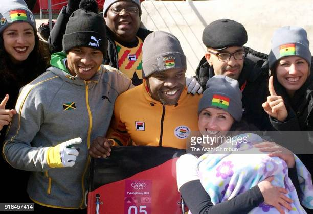 Akwasi Frimpong of Ghana poses for photographs with his wife Erica Shields Frimpong and Anthony Watson of Jamaica after the Men's Skeleton heats on...