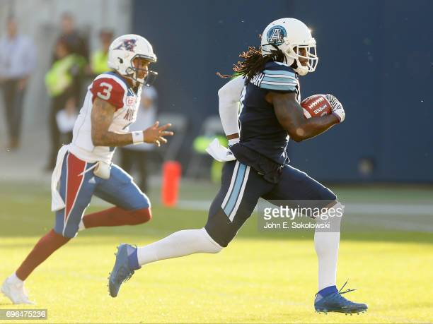 Akwasi OwusuAnsah of the Toronto Argonauts outruns Vernon Adams Jr #3 of the Montreal Alouettes to score a touchdown on an interception return during...
