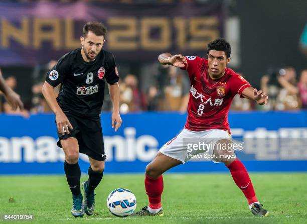 Al Ahli midfielder Everton Augusto De Barros Ribeiro fights for the ball with Guangzhou Evergrande midfielder Bezerra Maciel Junior during the AFC...