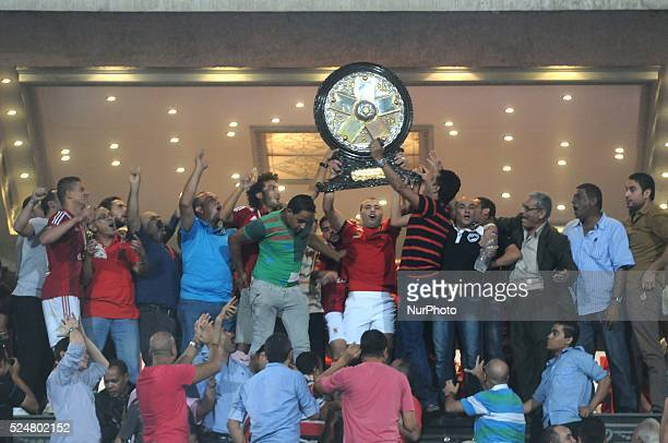 Al Ahly's Emad Metb celebrates with the trophy after his team won the Egyptian League title after the Egyptian Premier League soccer match at the...