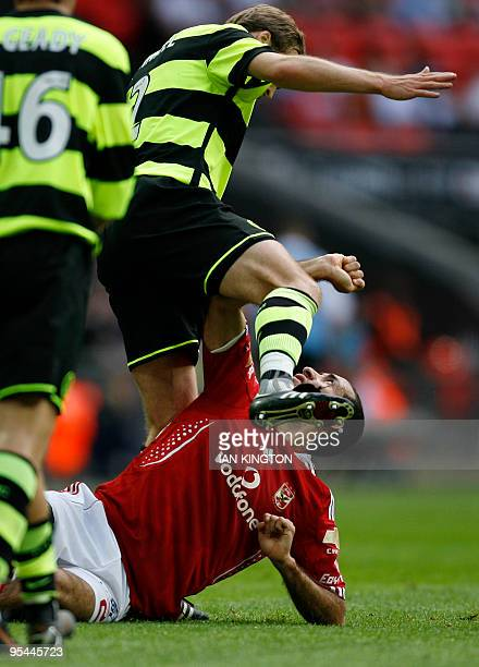 Al Ahly's Mohamed Aboutrika tangles with Celtic's German player Andreas Hinkel after a challenge during the Wembley Cup competition at Wembley...