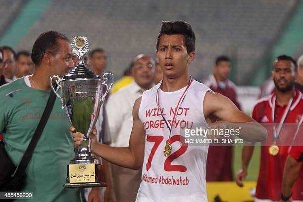 Al Ahly's player Amr Gamal celebrates with the trophy after winning the Egyptian Super Cup football match against Zamalek at the Cairo International...
