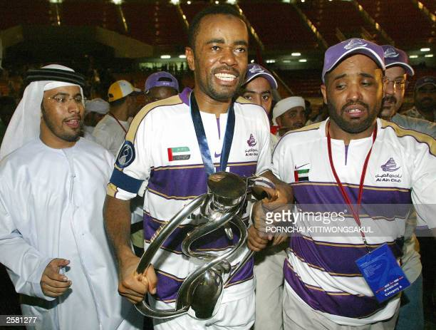 Al Ain player Salem Jawhar Salmeen J. Celebrates with the trophy during the AFC Champions League final, second leg in Bangkok, 11 October 2003. Al...