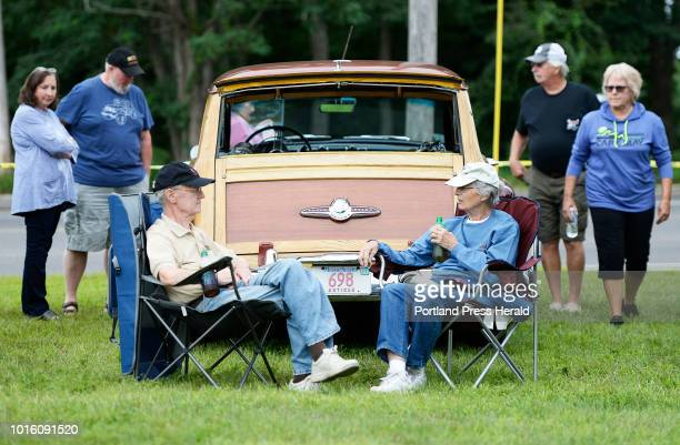 Al and Nancy Dann of Wayland Massachusetts sit in lawn chairs in front of their 1953 Buick Woody as people check out their car during the 7th annual...