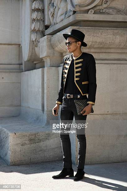 Al Barry wears black hat Saint Laurent black and gold frogged military jacket Saunt Laurent black jeans and Saint Laurent Black suede chelsea boots...