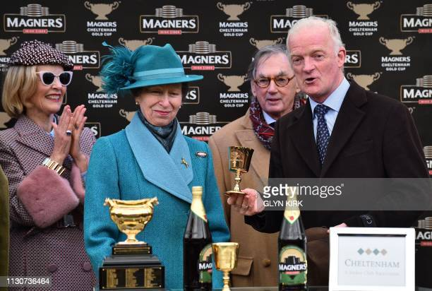 Al Boum Photo owner Mrs Donnelly aplauds as Britain's Princess Anne Princess Royal persesnts trainer Willie Mullins with a trophy after Irish jockey...